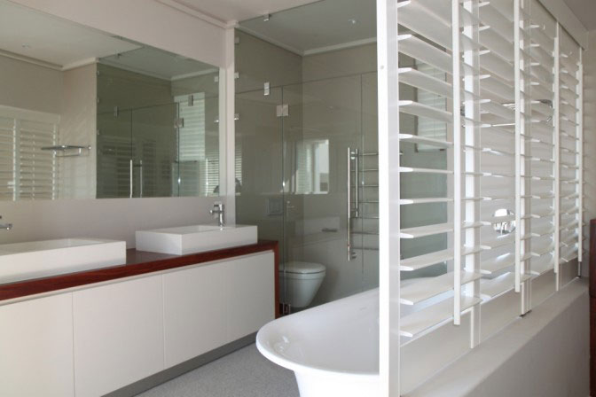 bath in bedroom with shutters divide